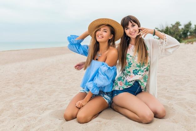 Eleganti belle donne sedute sulla sabbia durante le vacanze estive sulla spiaggia tropicale, stile bohémien, amici che viaggiano insieme, accessori di tendenza alla moda, emozione felice sorridente, umore positivo, cappello di paglia