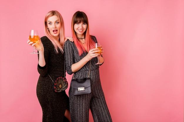 Eleganti donne che celebrano abiti da festa bevendo shampagne e si divertono insieme