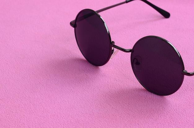 Eleganti occhiali da sole neri con occhiali rotondi si trovano su una coperta fatta di morbido e soffice tessuto in pile rosa chiaro.