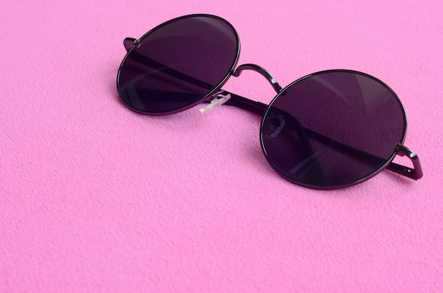 Eleganti occhiali da sole neri con occhiali rotondi si trovano su una coperta fatta di morbido e soffice tessuto in pile rosa chiaro