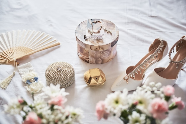 Eleganti scarpe da sposa bianche, profumo, fiori e gioielli.