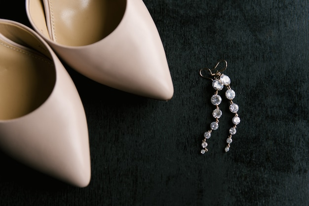 Eleganti scarpe da sposa ed eleganti orecchini in argento