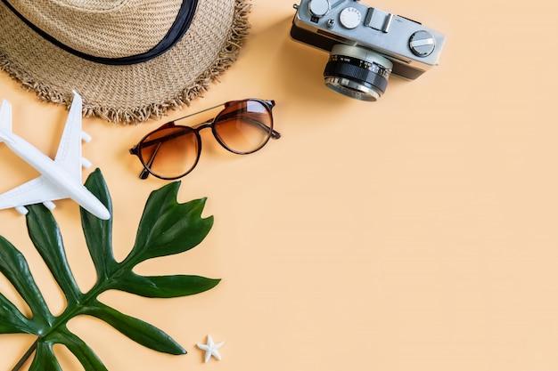 Elementi degli accessori di viaggio con il fondo di colore, concetto di vacanze estive