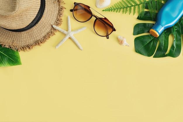 Elementi degli accessori di viaggio su fondo giallo, concetto di vacanze estive