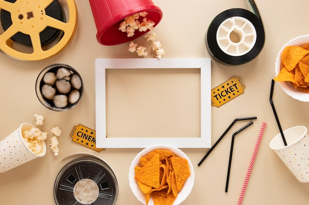 Elementi del cinema su sfondo beige con cornice vuota bianca