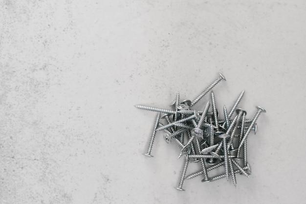 Elementi di fissaggio per l'edilizia, viti su uno sfondo grigio chiaro. copia spazio