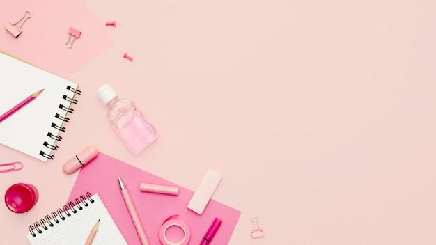 Elementi di scuola piatta laici su sfondo rosa
