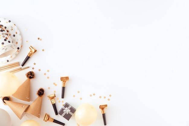 Elementi dorati del partito con i coriandoli su fondo bianco