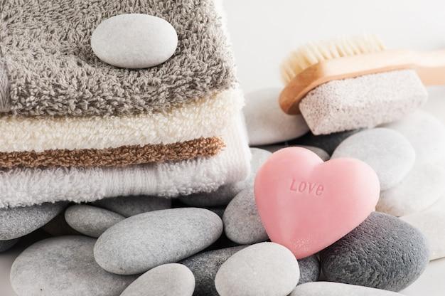Elementi spa con asciugamani, sapone cuore rosa e pomice