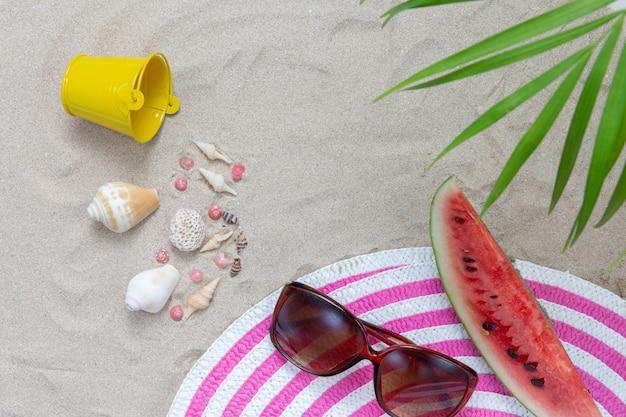 Elementi spiaggia sulla sabbia con anguria e occhiali da sole