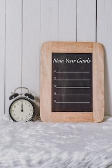 Elenco degli obiettivi del nuovo anno scritto sul taccuino con la sveglia