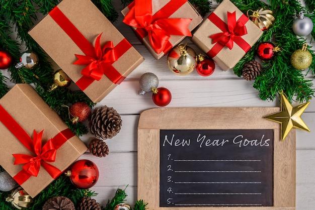 Elenco degli obiettivi del nuovo anno scritto sulla lavagna con l'albero di natale e la decorazione