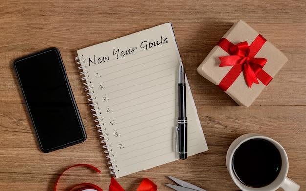 Elenco degli obiettivi di capodanno scritti su notebook con confezione regalo e smart phone