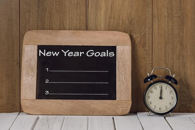 Elenco degli obiettivi di capodanno scritti sulla lavagna con la sveglia