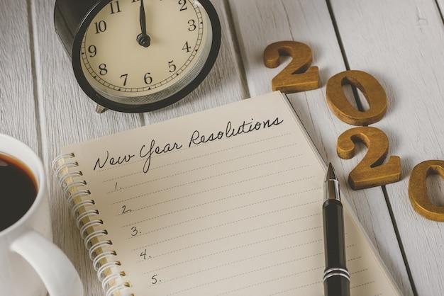 Elenco delle risoluzioni del nuovo anno scritto sul taccuino con sveglia, penna, caffè