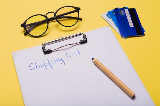 Elenco di carta con parole lista della spesa, carte di credito, penna su sfondo giallo. copia spazio spazio libero.