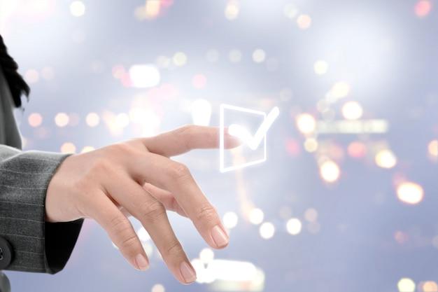 Elenco di puntamento donna d'affari per fare il segno di spunta sullo schermo virtuale