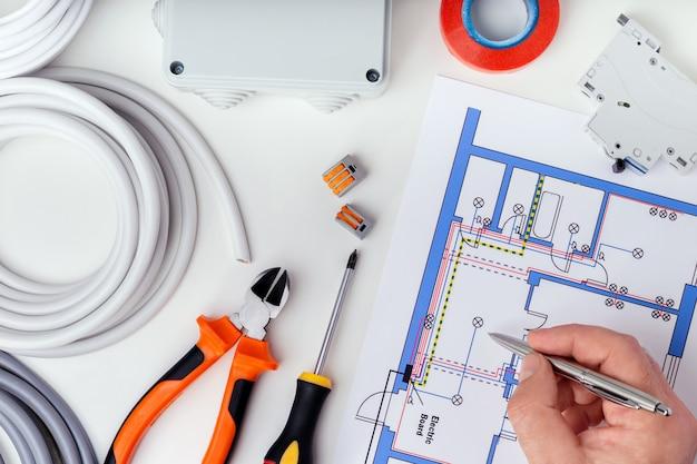 Elettricista che controlla i piani elettrici. riparazione di apparecchiature elettriche.
