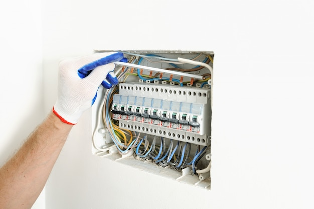 Elettricista che installa una scatola dei fusibili elettrica in una casa