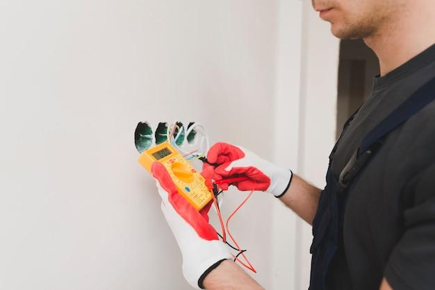 Elettricista che misura la tensione