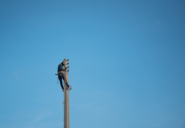 Elettricista che si arrampica palo elettrico