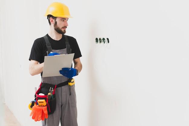 Elettricista con tavoletta di carta guardando i buchi