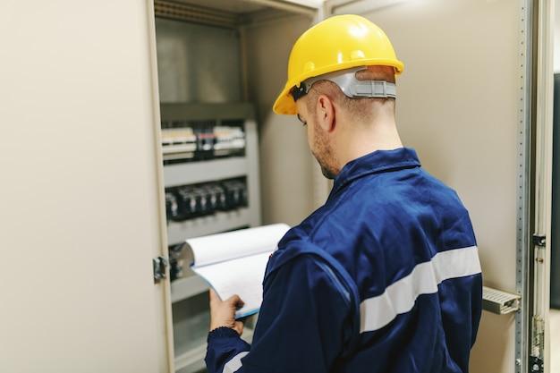 Elettricista in tuta protettiva e casco che tiene appunti e cercando di risolvere il problema tecnico mentre si trovava accanto al cruscotto nella pianta dell'industria pesante.