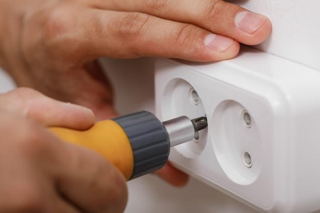 Elettricista installazione presa elettrica sulla parete con un cacciavite. avvicinamento