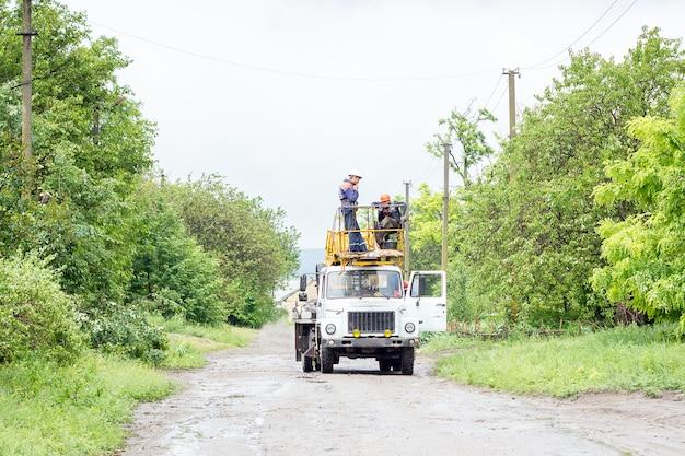 Elettricisti che lavorano su pali, un gruppo di lavoratori in veicoli speciali