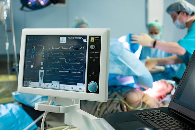 Elettrocardiogramma in sala operatoria di pronto intervento chirurgico ospedaliero che mostra la frequenza cardiaca del paziente con sfocatura squadra di chirurghi