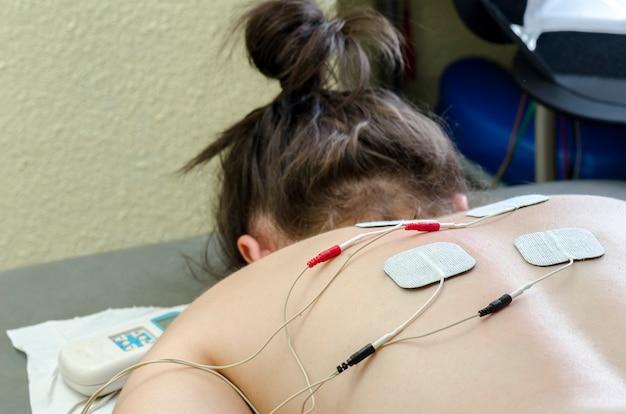 Elettrodi tens posizionati per il trattamento del mal di schiena in terapia fisica