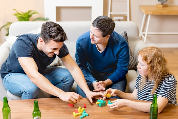 Elevato angolo di amici che giocano a casa e bevono birra