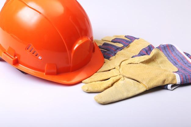 Elmetto arancione, occhiali e guanti di sicurezza su uno sfondo bianco.
