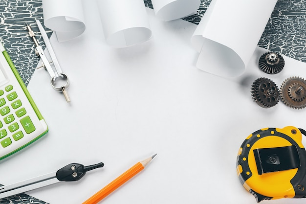 Elmetto di sicurezza e pergamene di disegni tecnici e materiali di consumo
