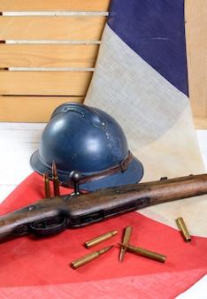 Elmetto francese della prima guerra mondiale con una pistola su una bandiera blu bianca rossa