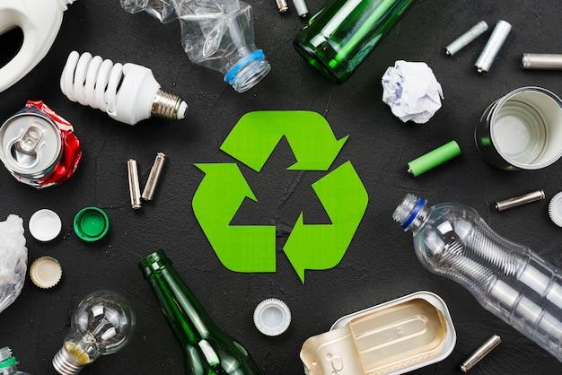 Emblema di riciclaggio intorno a rifiuti su sfondo nero