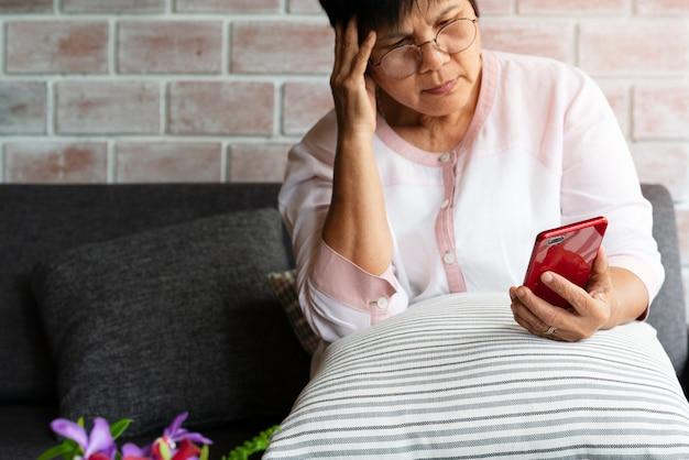 Emicrania della donna anziana mentre per mezzo dello smartphone, sanità