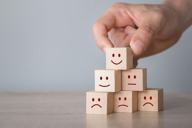 Emoticon del cliente che preme emoticon sul cubo di legno, valutazione di servizio, concetto di soddisfazione.