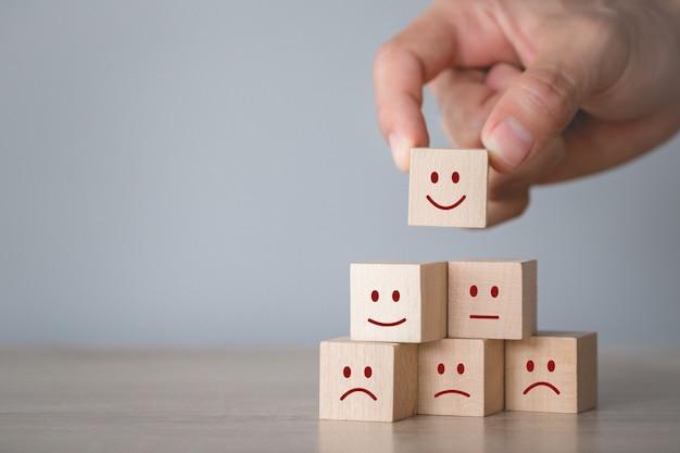 Emoticon del fronte di smiley che preme cliente sul cubo di legno, valutazione di servizio, concetto di soddisfazione.