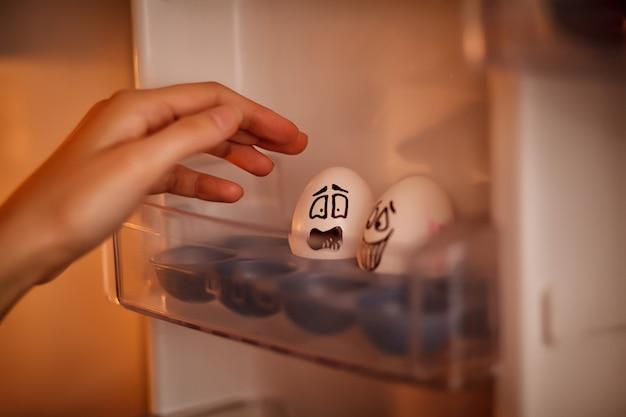 Emotionally eggs. una mano femminile prende un uovo emotivamente dal vassoio del frigo.