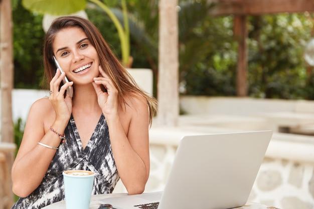 Emotiva donna bruna felice con espressione allegra parla con il migliore amico su smart phone, discutere insieme lo shopping online, navigare in internet webstore, si siede al caffè all'aperto con caffè aromatico