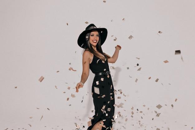 Emotiva donna elegante che indossa il cappello che celebra la festa in elegante abito nero. ragazza efficace che mostra il suo bel sorriso e balli