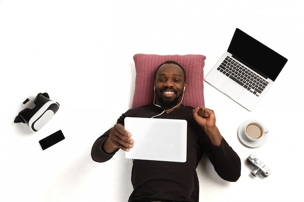 Emotivo uomo afro-americano con gadget, tecnologie. dispositivi che collegano le persone durante la quarantena