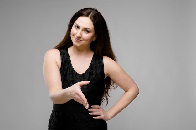 Emozionale piuttosto amichevole positivo plus size modello in piedi in studio offrendo stretta di mano su sfondo grigio
