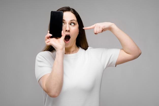 Emozionale sorridente felice plus size modello in piedi in studio guardando in camera offrendo il telefono cellulare ad un cliente