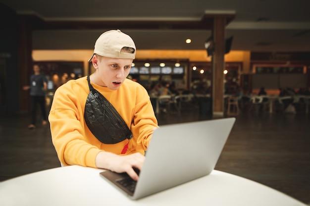 Emozione giovane libero professionista in abbigliamento casual lavora in un centro commerciale