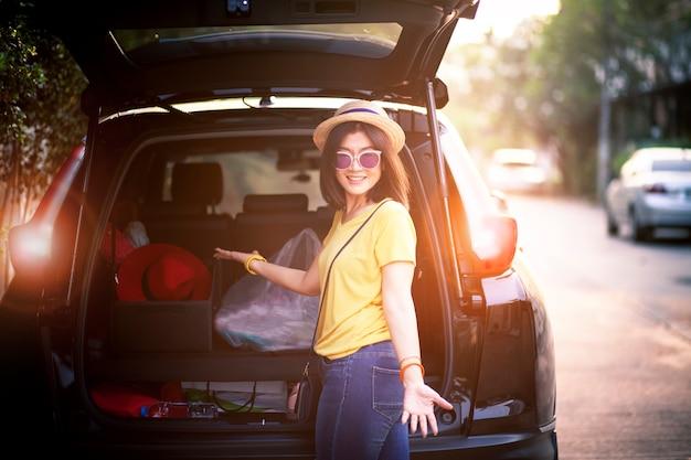 Emozione sorridente a trentadue denti di felicità del fronte della donna del viaggiatore che sta dietro all'automobile del suv pronta per il viaggio stradale sul tempo di vacanza