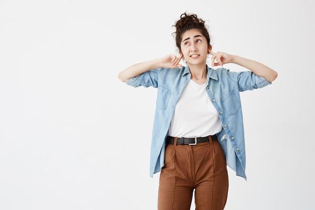 Emozioni negative, stress mal di testa e frustrazione. giovane donna dai capelli scuri frustrata stressata vestita in camicia blu che copre le orecchie con le mani e chiude gli occhi a causa del rumore
