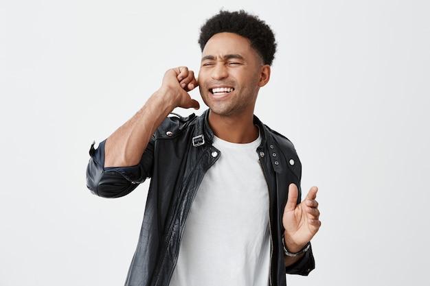 Emozioni positive. chiuda sul ritratto di bello studente maschio dalla pelle scura maturo che collega l'orecchio con il dito, chiudendo gli occhi, cantando nel karaoke la sua canzone preferita.