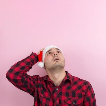 Emozioni sul viso, paura, ricordi di vacanza, negativi. un uomo in un coniglio plaid e un cappello rosso di natale